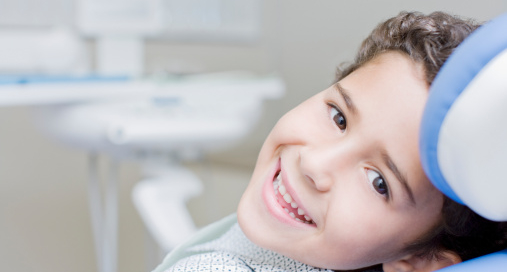 Boy smiling and sitting in dentists chair
